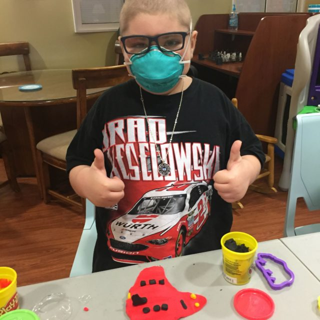Patient Ollie making play dough and giving two thumbs up