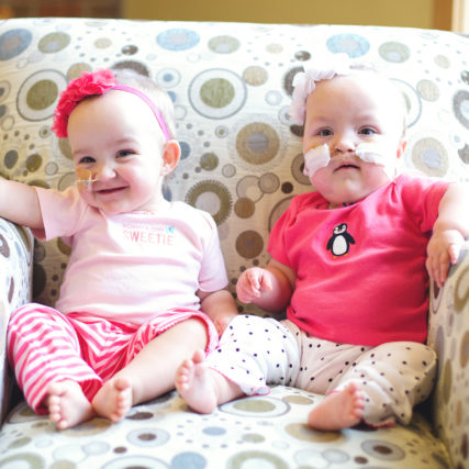 Young Twin girls in pink outfits on a chair together