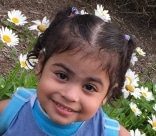 Marialena smiling with flowers in the background
