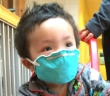 Young boy named Ryan wearing a hospital mask