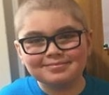 Ollie, a young boy wearing glasses, smiling