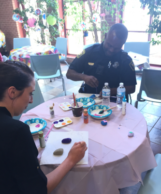 Police officer and staff member painting rocks