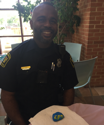 Cincinnati police officer with blue and gold painted rock