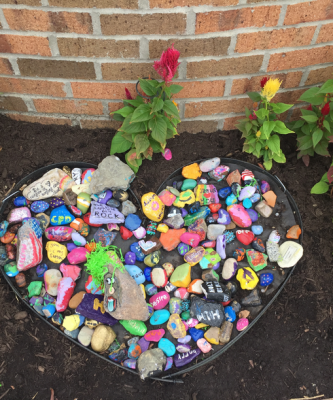 Heart shaped garden filled with various painted rocks