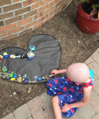 Young girl putting painted rocks in RMH House rock garden that is shaped like a heart