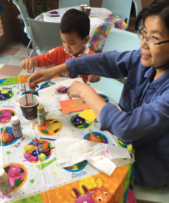 Mother and son painting rocks at a table