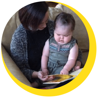 Young girl sitting on her mom's lap as they read a book