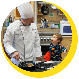 Young boy with an oven mitt in the kitchen with a chef
