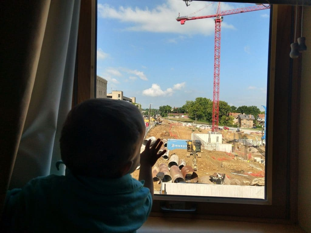 little boy looking out a window at construction