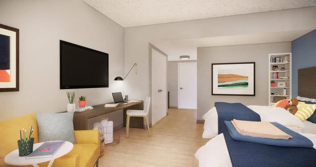 Entry view of new suites for expansion with two beds, a television, chairs, bookshelves and doors