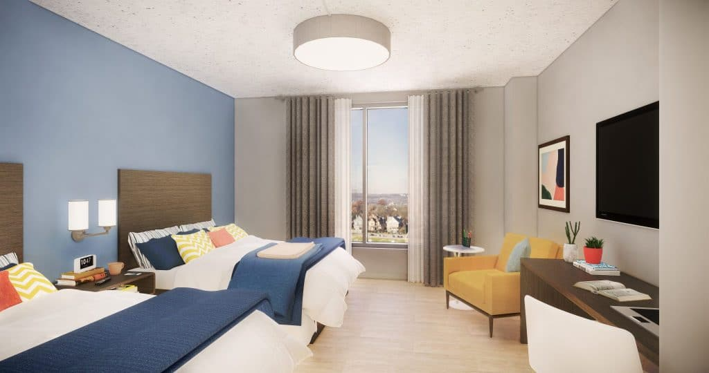 Window view of new suites showing two beds, chair, desk, television, wall lamps