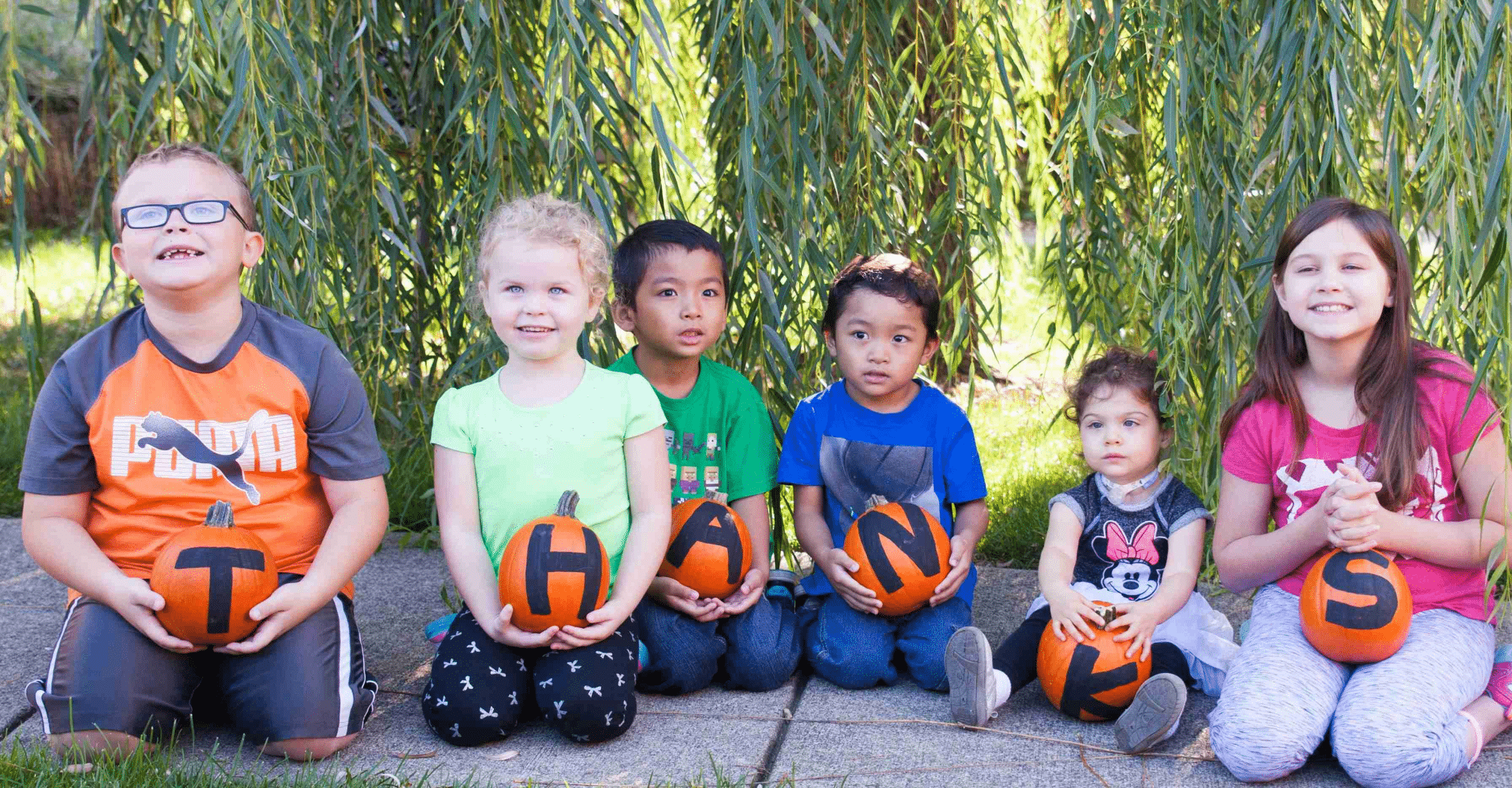 "Group of guest children holding pumpkins that spell ""thanks"""