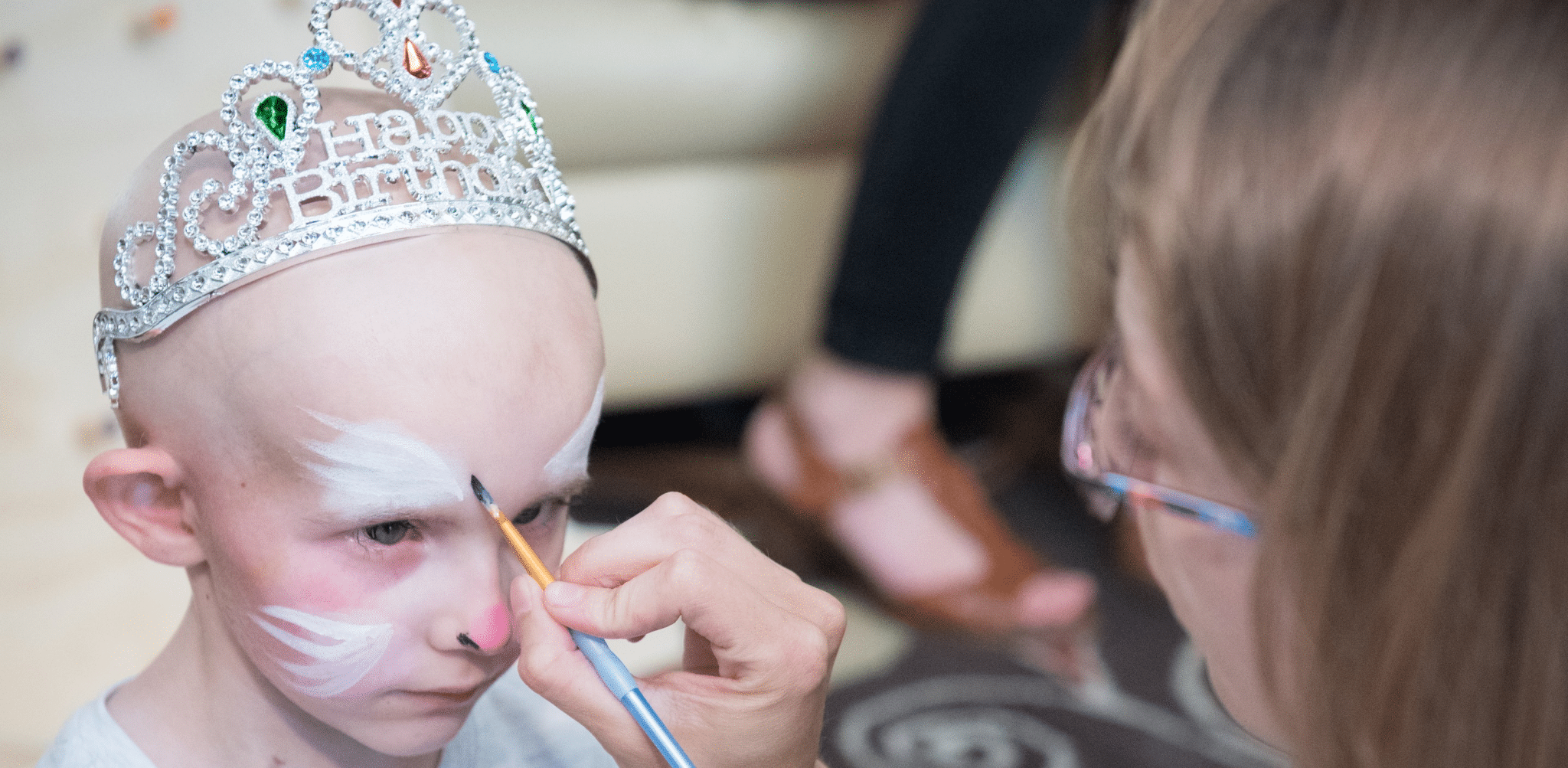 Young girl with no hair having face painted
