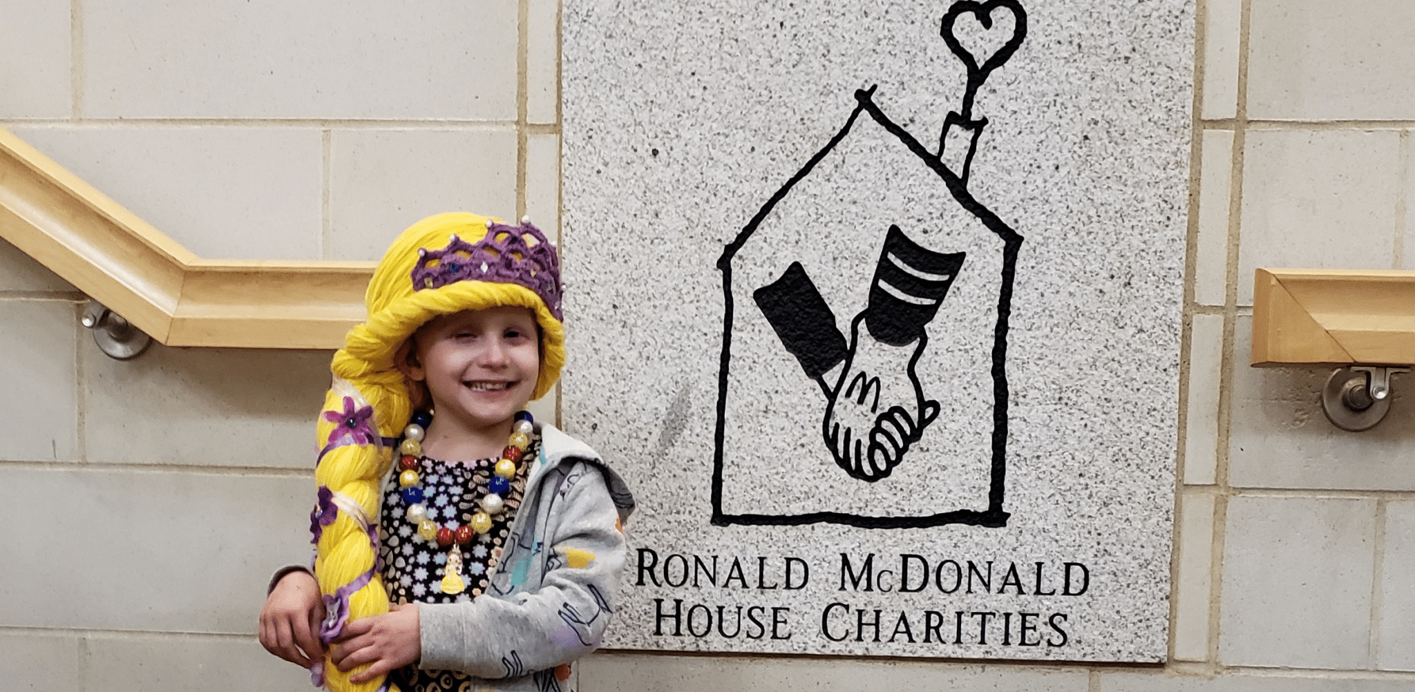 Young girl in yarn wig smiling by RMH logo on wall