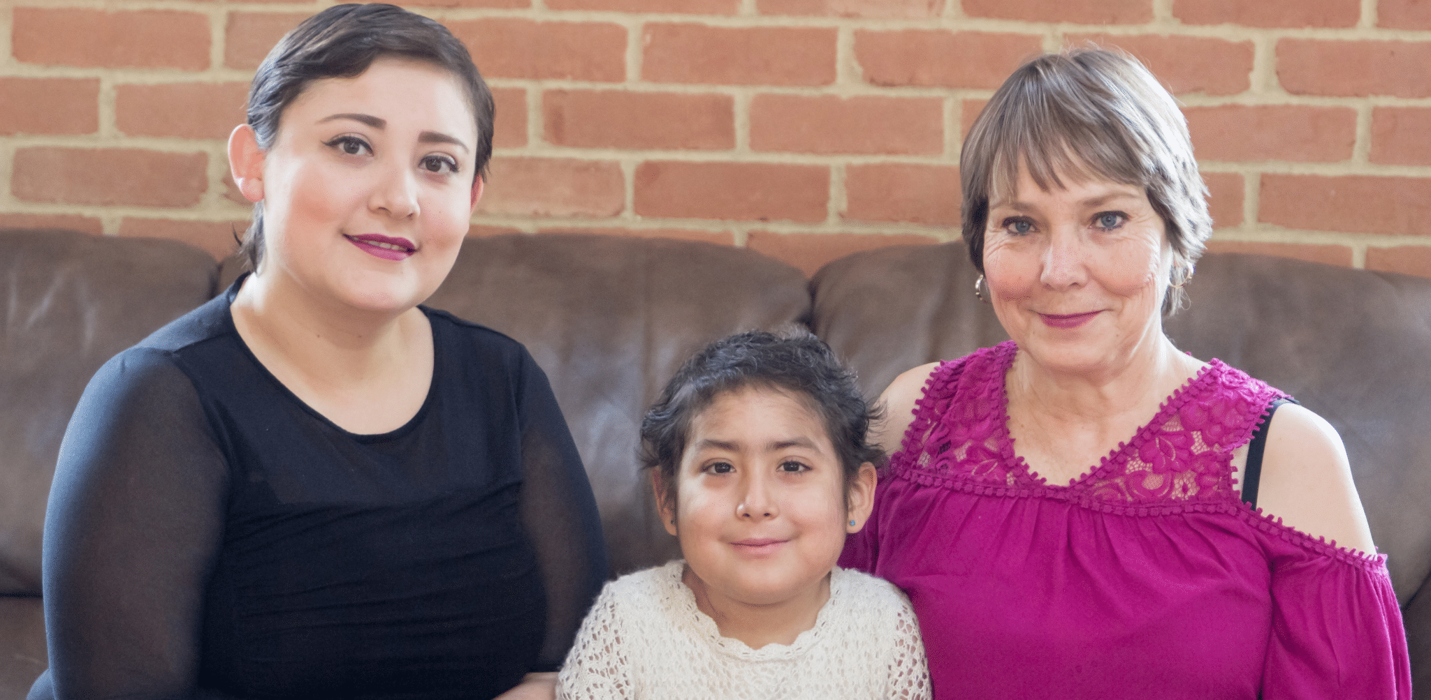 Mother, grandmother and daughter smiling on couch
