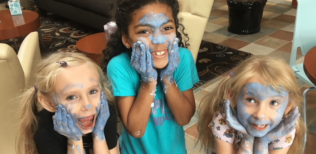 Three guest children, younger girls, smiling with faces covered in paint and hands on their faces