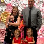 Mother, son, father and twin girls smiling in formal attire in front of a floral backdrop