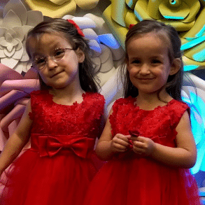 Three-year-old twin sisters in formal red dresses posing in front of floral background.