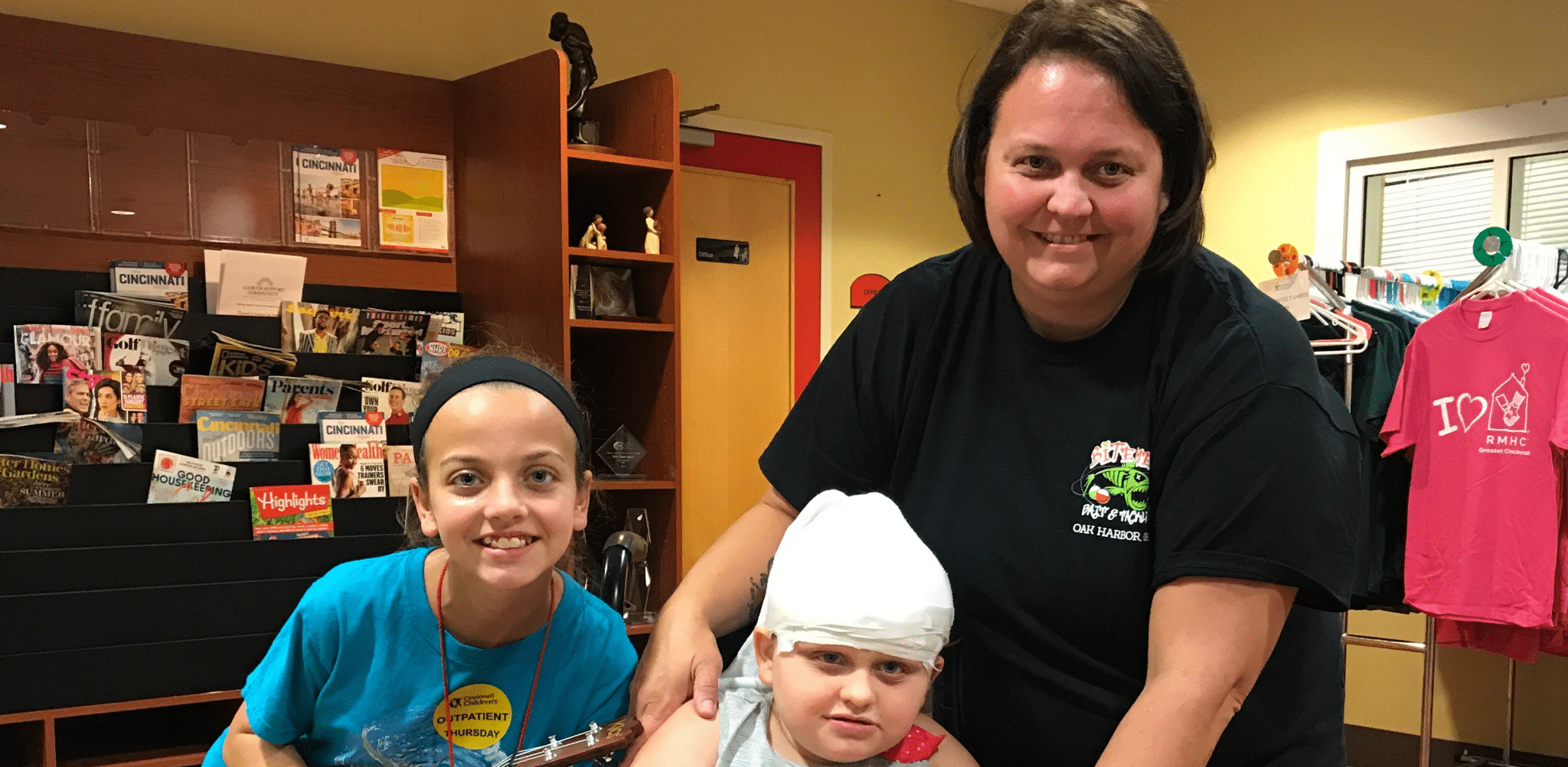 Woman posing with two children, one with head wrapped in bandages