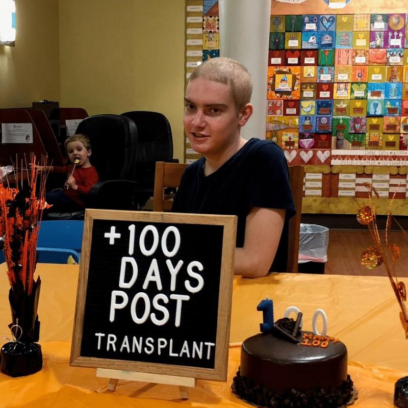 Teenage boy with cake and celebration sign