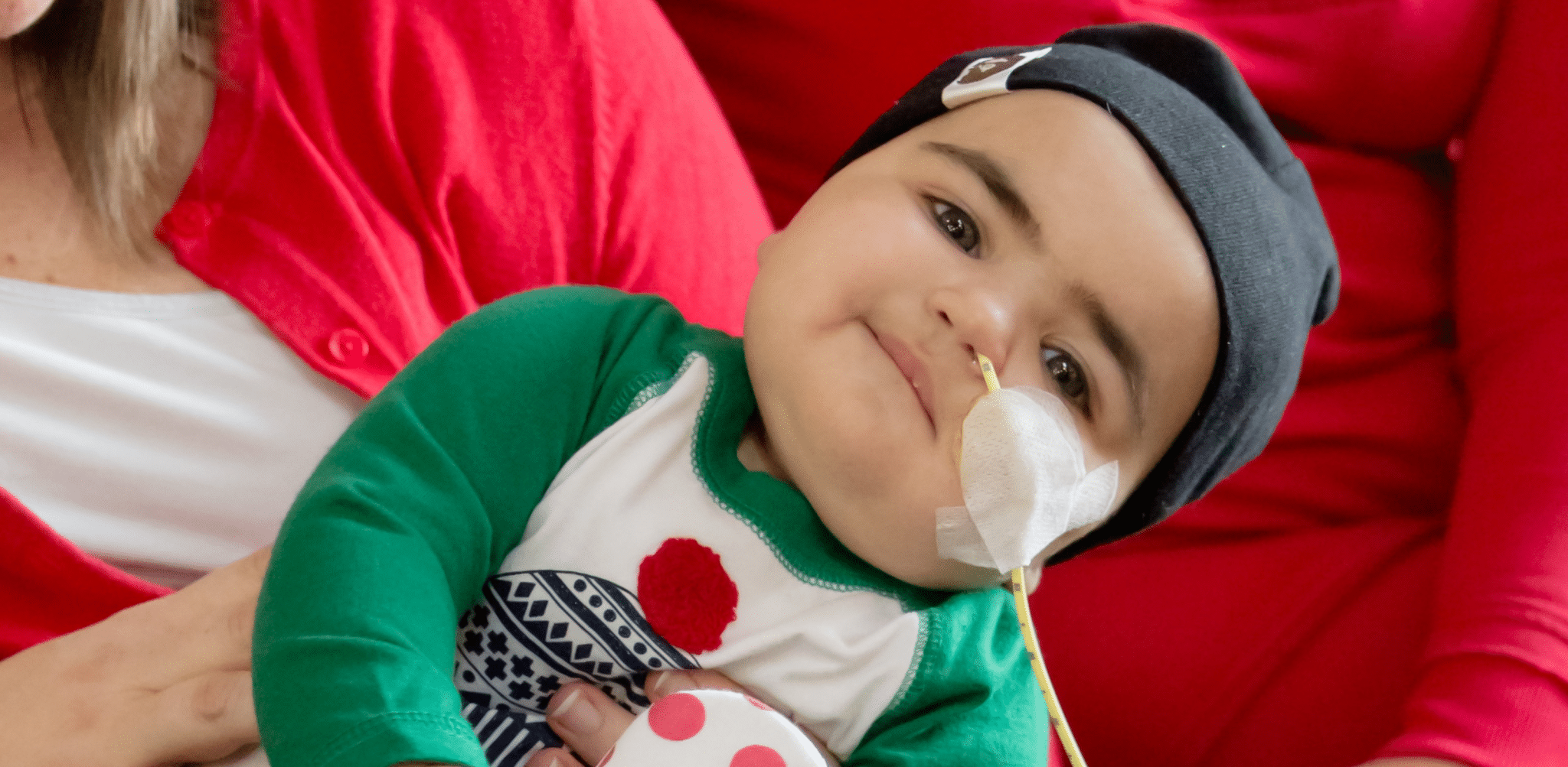 Young child with NG tube smiling, heart sticker holding tube onto face