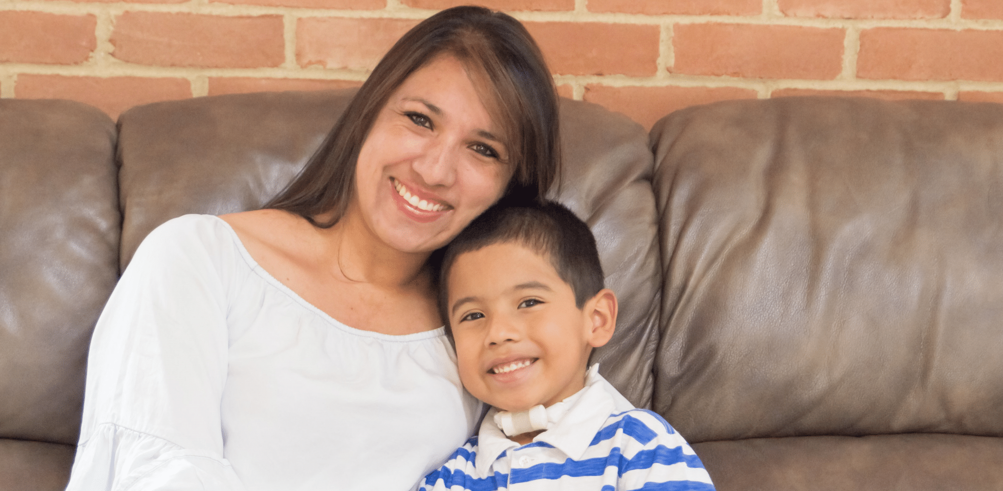 Mother and son with trach smiling on couch
