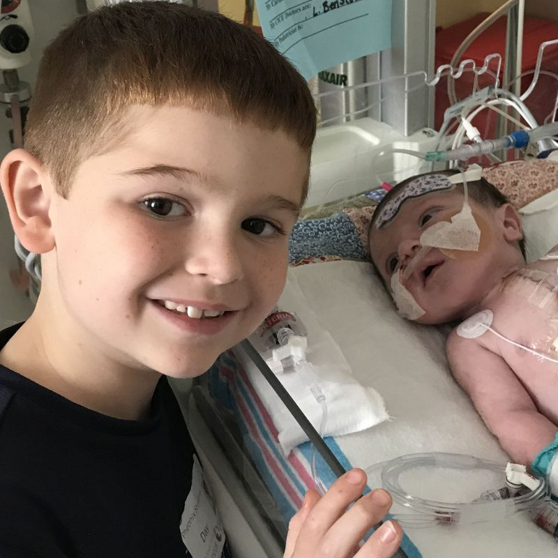 Big brother posing with baby brother who is in hospital with tubes.