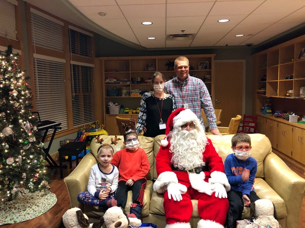 Mom, dad and three sons sit on a couch with Santa