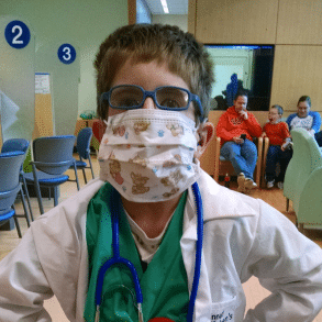 Young boy wearing mask and dressed up as a doctor