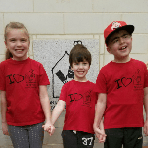 Blake with his twin sister and younger brother all wearing matching red RMH shirts.