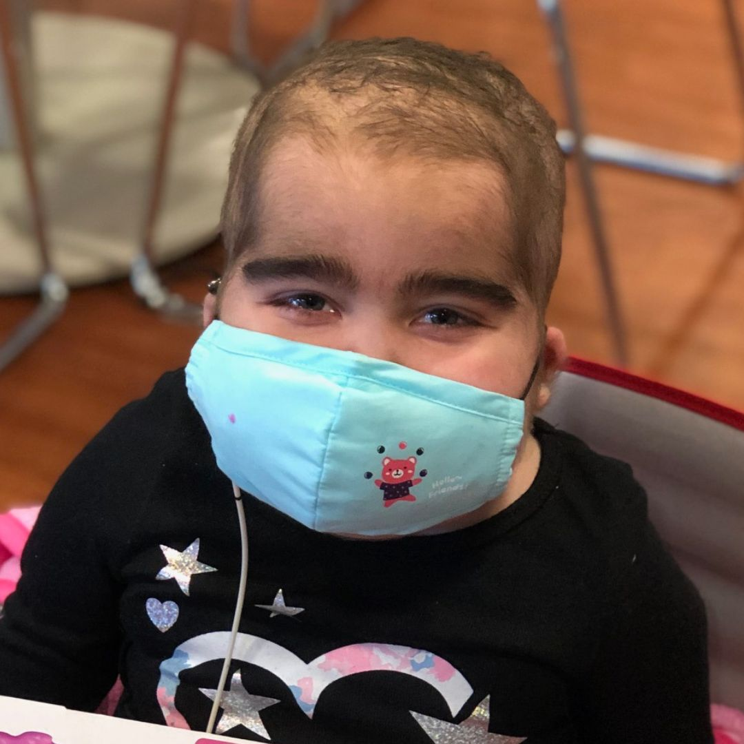 Young girl with blue hospital mask on smiling