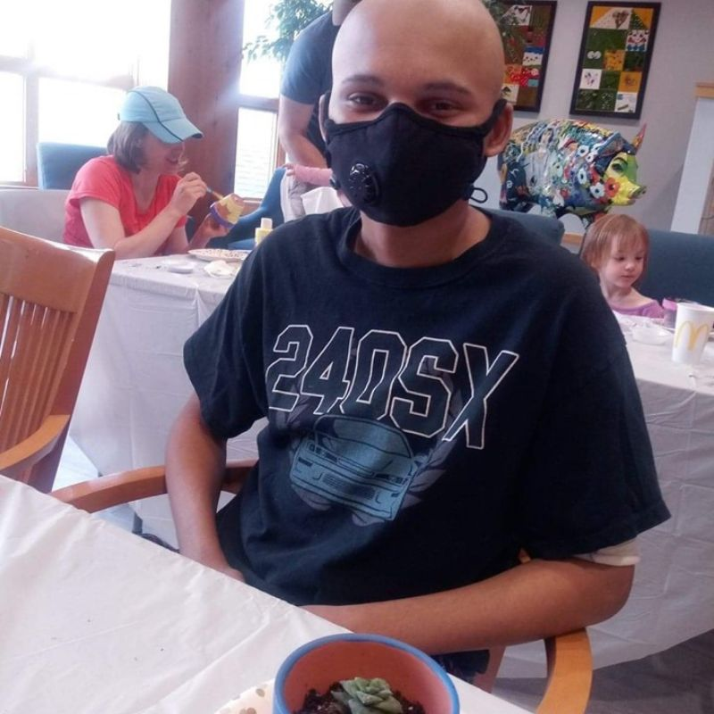 Teenage boy with mask on sitting at a table