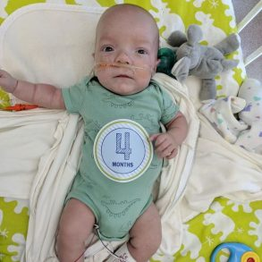 Picture of baby Elijah in the hospital wearing a four month old sticker.