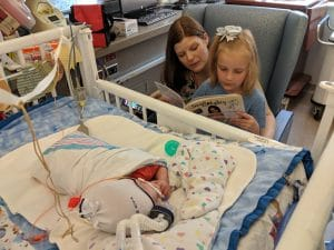 Claire and Abby reading to baby Elijah in the hospital.